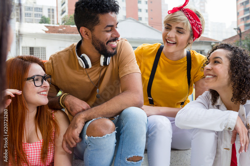 Mixed race group socializing in a party at restaurant outside. Summer, warm, friendship, diversity, reunion concept.