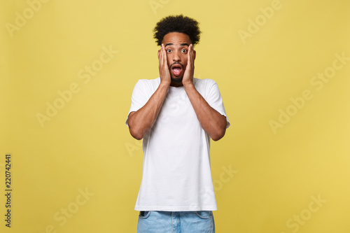 Fényképezés  Emotional and People Concept - Portrait of excited young African American man screaming in shock and amazement holding hands on head