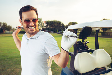 Closeup portrait of man smiling while holding golf club