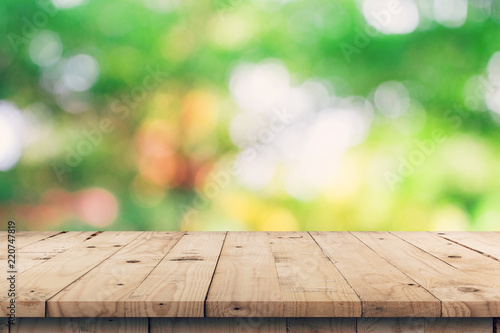 Foto  Empty wooden table top and green bokeh display montage for product with space