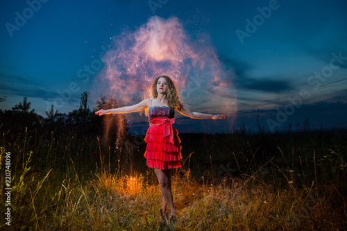 Poster Bleu nuit A girl in a black top and red skirt conjures up in a field during photoshoot with flour during sunset