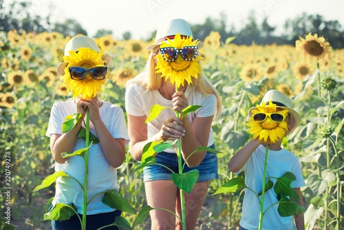 Obraz Mom and sons are walking around the field with sunflowers. A happy day. - fototapety do salonu