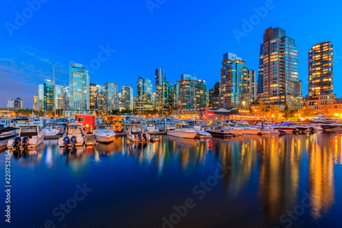 Photo Stands Sunset at Coal Harbour in Vancouver British Columbia with downtown buildings boats and reflections in the water