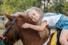 A Cute Little Blonde Girl Is Sitting On A Pony In Autumn.