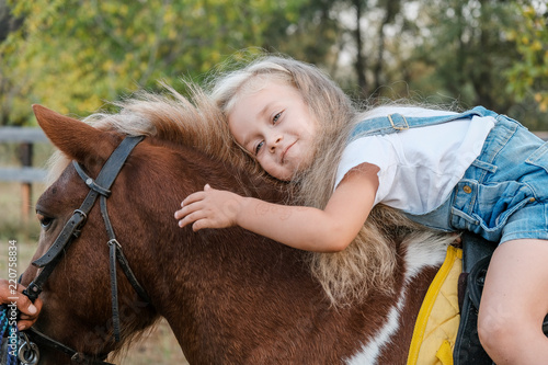 Fototapeta A cute little blonde girl is sitting on a pony in autumn.