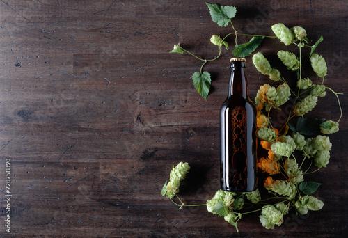 Tuinposter Bier / Cider Bottle of beer and hops on a old wooden background.