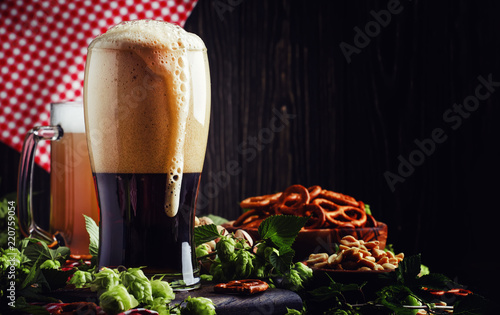 In de dag Bier / Cider Dark German beer is poured into a glass, fresh green hops and bowls with salty snacks and nuts, autumn beer festival concept, dark background, selective focus