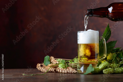Tuinposter Bier / Cider Mug of beer, grain and hops on a old wooden table.