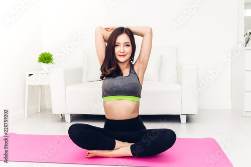Sport woman wearing sportswear bra and pants sitting relax on pink mat and do fitness exercise and practicing yoga at home.Diet concept.Fitness and healthy lifestyle