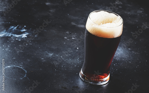 Foto auf Leinwand Bier / Apfelwein Dark english beer, ale or stout is poured into glass, dark bar counter, space for text, selective focus