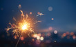 canvas print picture - Sparkler with blurred busy city light background