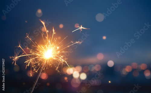 Fotografía  Sparkler with blurred busy city light background