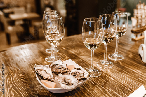 Oysters with lemon and glasses of wine in the seafood restaurant