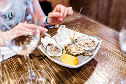 Woman eating oysters and shellfish in restaurant. Delicious and delicacy Seafood cuisine