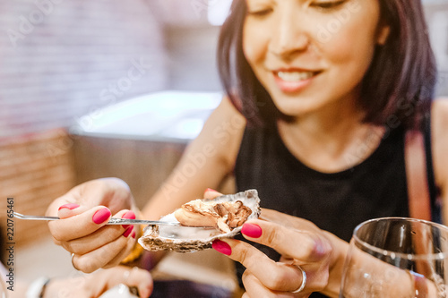 Woman eating a delicacy oyster, close-up at a restaurant