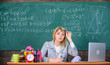 Teacher doubtful face listening you. She has doubts in your report or knowledge. Teacher woman sit table classroom chalkboard background. Teacher suspiciously peeking out of eyeglasses
