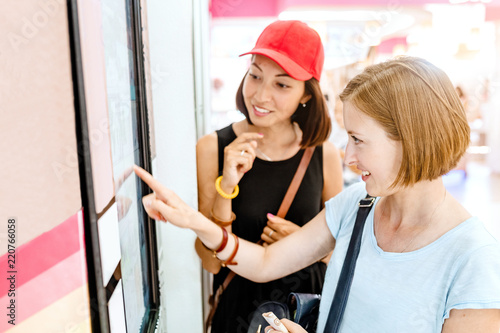 Two friends woman using automated self-service machine with big digital touch screen Wallpaper Mural