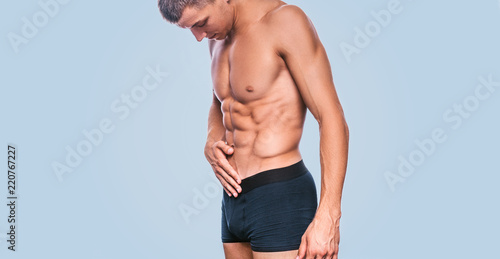 Fotografia Side view of fitness male model in black underwear showing his abdominal torso on a blue background