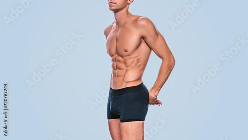 Fotografia Image of fitness male model in black underwear showing his abdominal torso on a blue background