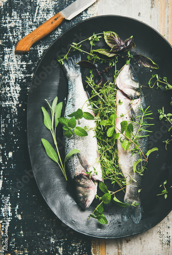 Cooking fish dinner. Flat-lay of raw uncooked sea bass fish with green herbs on black plate over rustic wooden painted background, top view, square crop. Helathy, clean eating, dieting food concept