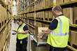 Coworkers working on aisle amidst racks at distribution warehouse