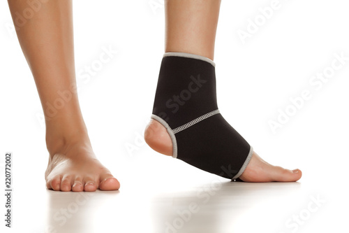 Photo Female leg with Supportive Orthopedic Wrist on the ankle on white background