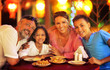 canvas print picture - Portrait of a family sitting at table at cafe and having dinner
