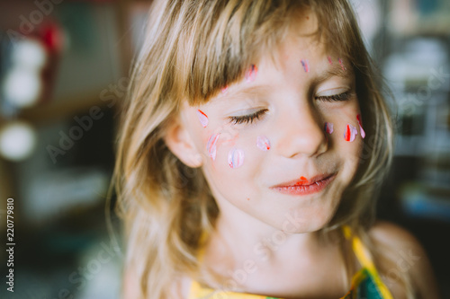 Fotografiet  Portrait of adorable little girl with paints on face .
