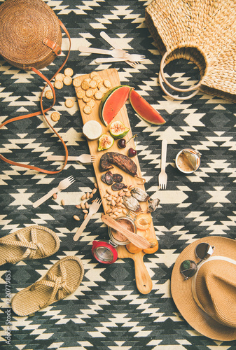 Summer picnic setting. Flat-lay of fresh fruit, smoked sausage, nuts, brie cheese, pate, cracker and woman straw accessories over linen blanket background, top view. Outdoor gathering or lunch