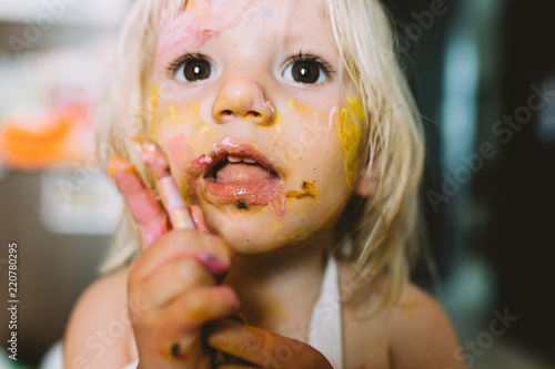 Fotografiet  Portrait of adorable baby girl painting  at home .