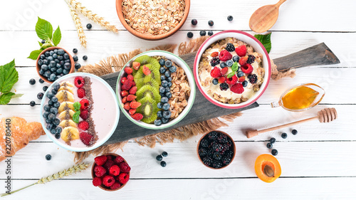 Fototapeta Large Assortment of porridge with fruit and berries. Breakfast. On a white wooden background. Top view. Free space for text. obraz