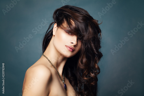 Stylish brunette woman on blue background with copy space