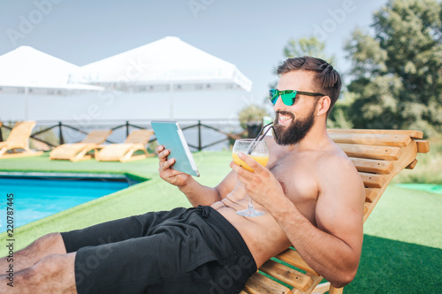 Relaxed and happy guy sits on sunbed and smiles Wallpaper Mural