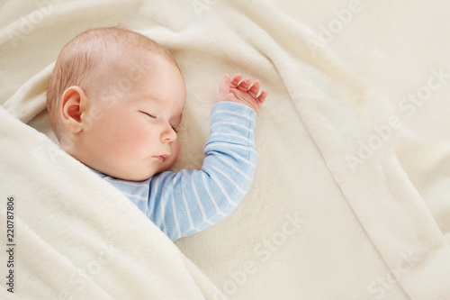 Baby sleeping covered with soft white blanket