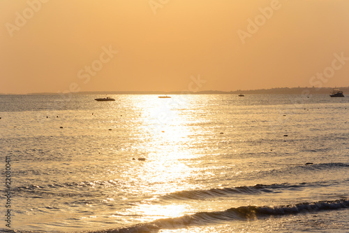 waves on the evening sea. strip of light from the sun. silhouettes of boats. the mountains on the horizon. orange tones