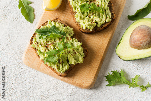 Two toasts with avocado and green salad on breakfast Canvas Print