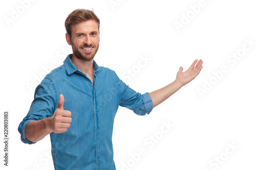 Photographie  smiling young casual man presenting and making the ok sign