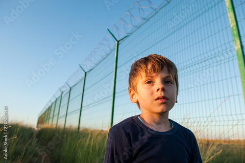 Foto  dramatic portrait of little kid refugee on high fencing barbed wire backdrop