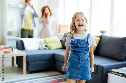 Photo Little girl in casualwear crying and shouting while her parents shutting their e