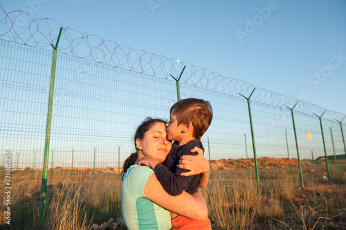 Canvas Print happy mother refugee reunited with child kissing her near fence barbed wire