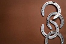 Pile Of Horseshoes Isolated On A Brown Background