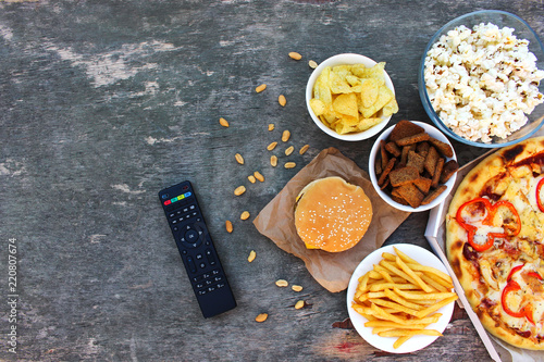 TV remote control, fast food on old wooden background. Concept of junk eating. Top view. Flat lay.  . © Victoria М
