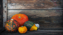 Different Pumpkins On Shabby Old Wooden Ground