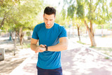 Man Checking Counts Of Steps On Smart Watch In Park
