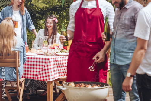 Close-up of men standing and talking over a grill with shashliks. Beautiful woman sitting by a birthday party table in the background.