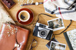 Top view of a table with a camera, coffee, leather bag, photos, glasses, and scarf