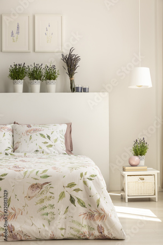 Lamp Above Cabinet Next To Bed With Plants On Headboard In ...