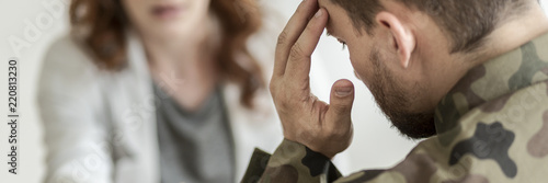 Obraz Close-up of a sad soldier with PTSD talking about his fears with a psychiatrist sitting in blurred background - fototapety do salonu
