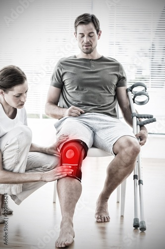 Tela Composite image of physiotherapist examining man with crutches