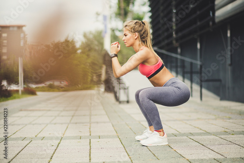 Women exercise squats. Side view. Fototapet